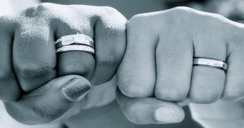 Two male hands as fists showing wedding rings