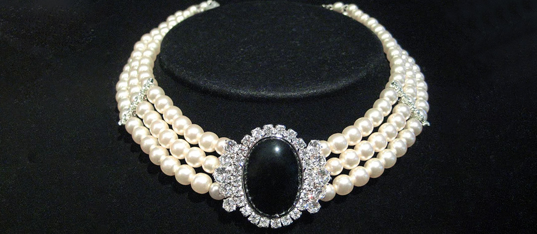 3 string pearl necklace with halo of diamonds around a centre stone on a black velvet background