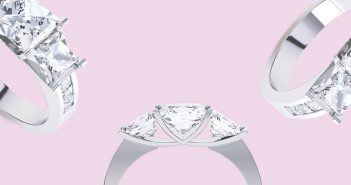 Three princess cut diamond rings scattered on pink background