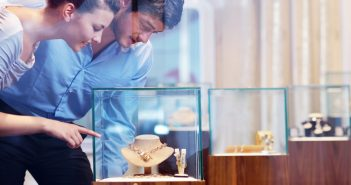 Couple buying jewellery pointing at necklace in display case