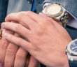 3 male hands on-top of each other with Rolex watches on their wrists
