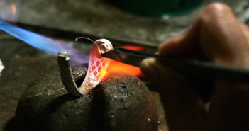 Image of Goldsmith creating a metal ring in a flame with a stone base.