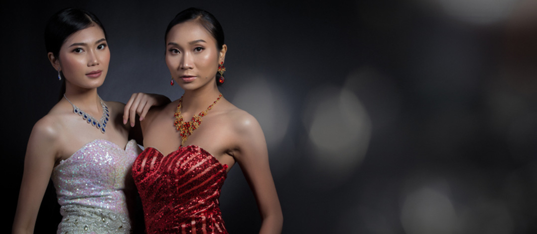 Two Asian women with statement necklaces in ruby and sapphire and diamonds with matching ruby and sapphire colour cocktail dresses on a dark background