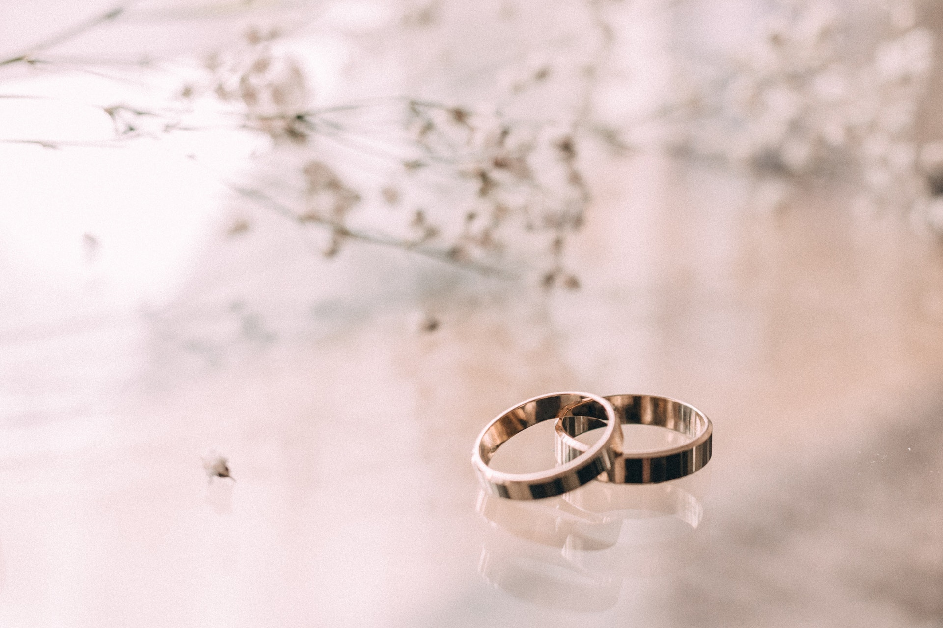 two wedding rings sitting on reflective table with small branch with little white flowers blurred in background