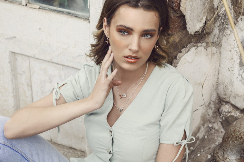 Model wearing humming bird necklaces, earrings sat against a stone wall
